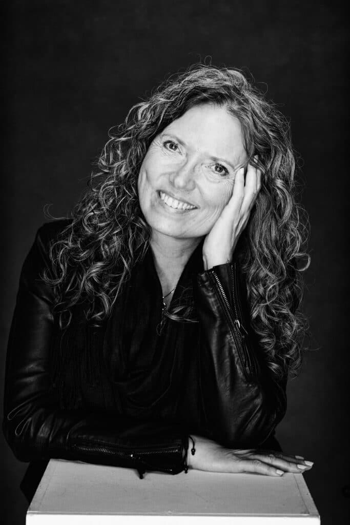 Portrætbillede af Gitte, hun sidder med hovedet på skrå og hånden på kinden og ser glad ud