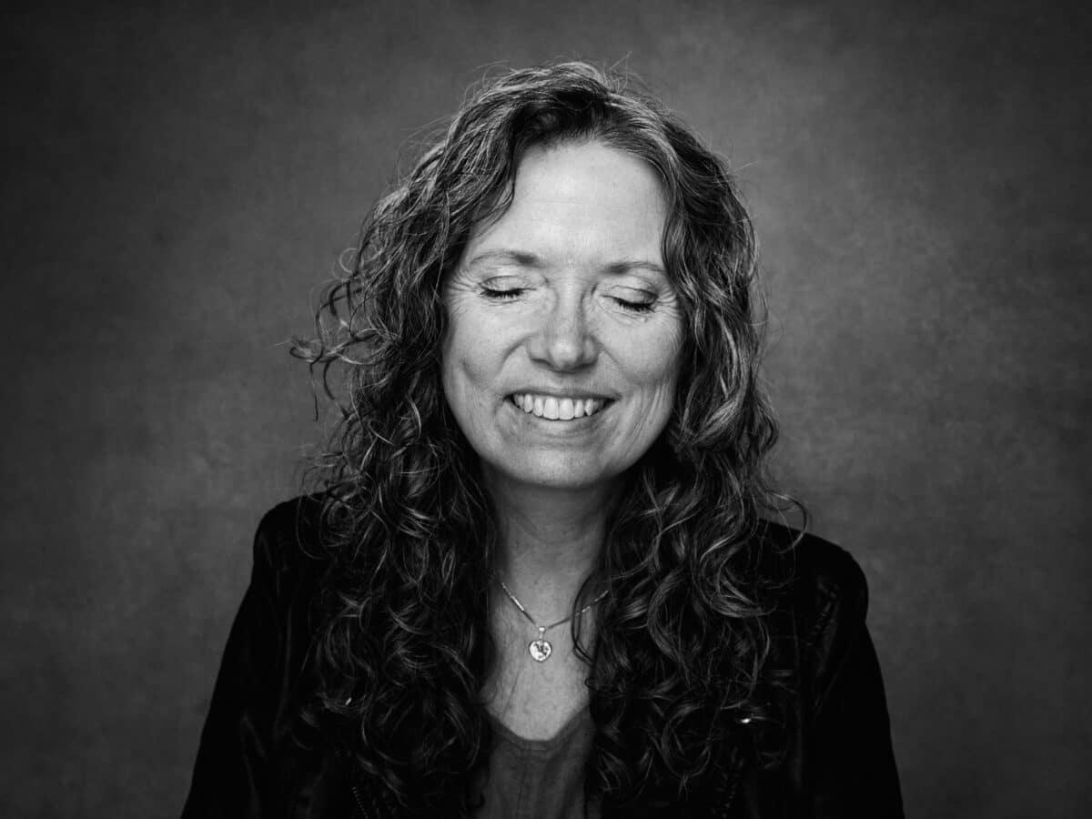 Portrætbillede af Gitte, hun sidder med lukkede øjne og ser tilfreds ud